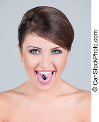 Young woman with a tablet on her tongue