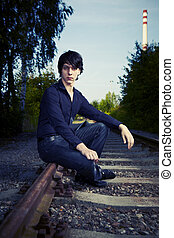 Is he waiting for train? - Moody young man acting his...