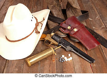 Revolver - A bunch of cowboy gear on a wooden background.
