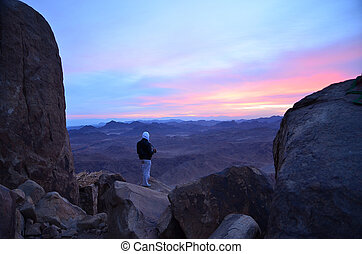 A man with a video camera meets dawn on Mount Moses, Egypt