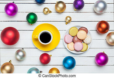 Cup of coffee and macaron with christmas toys on whte...