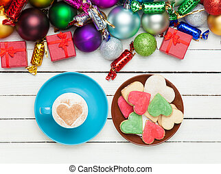 Cup of coffee and cookie with christmas toys on whte...