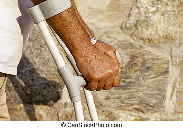 crutches - arms of older man leaning on crutches