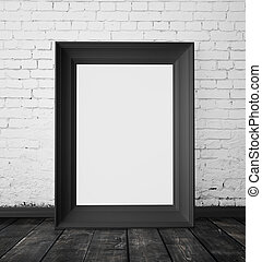 blank frame hanging on a white brick wall