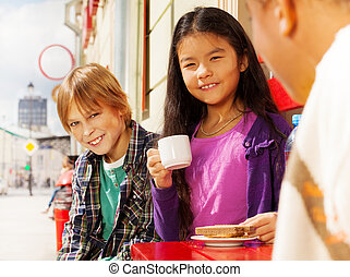 Asian girl and blond boy sitting outside in cafe