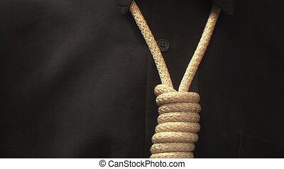 man pulls a rope noose around his neck