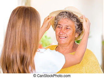 Elderly home care - Caregiver put the hat on the happy...