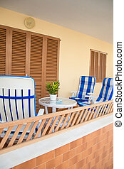 Mediterranean apartment terrace exterior with chairs.