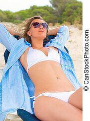Young woman sunbathing on a lounger.