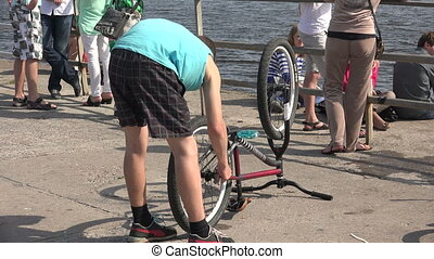 The young man looks at the bike 4K - The young man looks at...