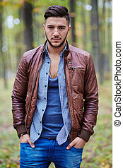 Fashionable young man in leather jacket outdoor in a forest