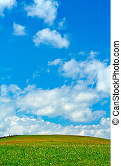 Green field, blue sky and white clouds, background