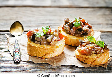 bruschetta with roasted eggplant and tomatoes on a dark wood...