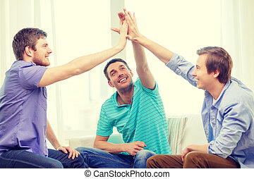 smiling male friends giving high five at home - teamwork,...