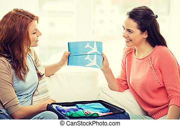 two smiling teenage girls with plane tickets - travel,...