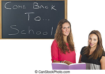 Two beautiful teenage students studying in the school