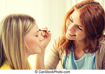 two smiling teenage girls applying make up at home - makeup,...