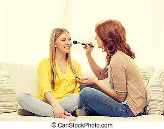 two smiling teenage girls applying make up at home - makeup,...