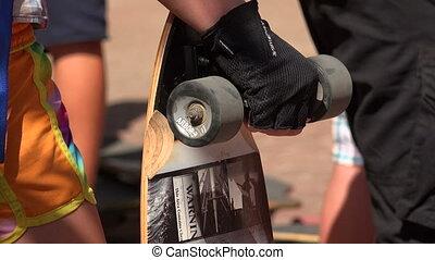 Skateboard in his hand. 4K.