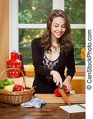 Health food. - Gorgeous young brunette woman in the kitchen...