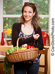 Eat healthy - Young brunette beauty in the kitchen with...