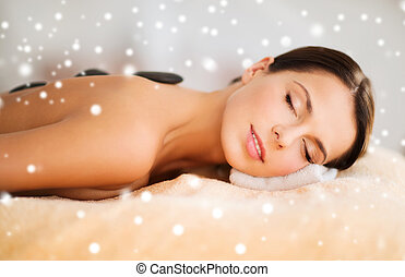 woman in spa salon with hot stones - beauty, health, people...