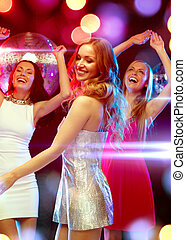 three smiling women dancing in the club - new year...
