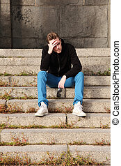 Man feeling depressed sitting down - A young man wearing...