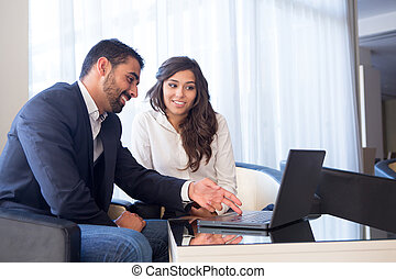 Business couple with computer - Young business couple...