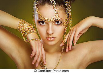 Girl with golden make-up and decoration of gold chains