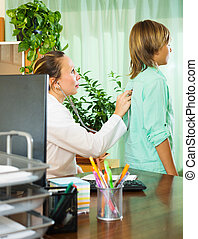 doctor with stethoscope examining teenager boy in office