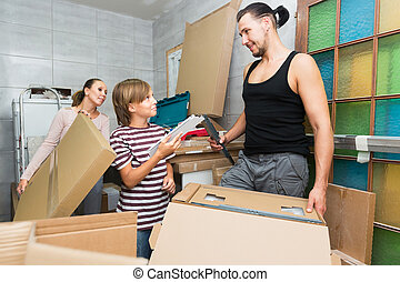 mother, father and son packing boxes - Young mother, father...