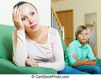 middle-aged woman and teenager son having conflict at home