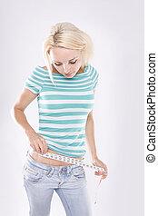 Fitness Girl measuring her stomache