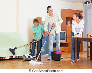 Cleaning - Happy family of three doing house cleaning with...