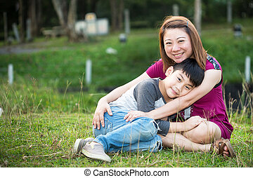 Son hugging mother Asian family in the park
