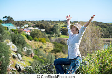 Woman in nature with arms outstretched