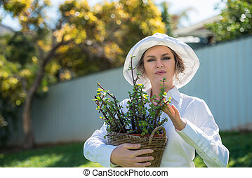 Woman holding a pot with plant