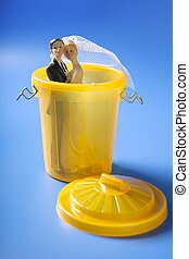 Wedding figurione on the yellow trash, divorce metaphor