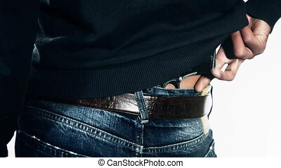 Man holding gun in pants - man`s back with gun tucked in...