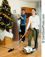 Couple cleaning with vacuum cleaner - Happy adult couple...