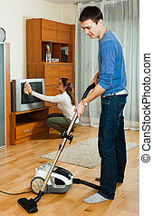 Happy family doing housework together in home