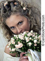 Bride smiling behind bouquet