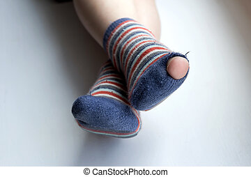 Worn out socks. Worn socks with a hole and a finger sticking...
