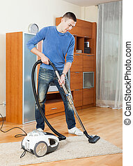 man  cleaning with vacuum cleaner in living room