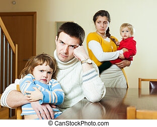 Young couple with children in quarrel at home - Young couple...