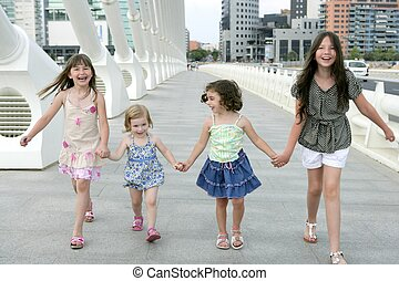Four little girl group walking in the city bridge downtown...