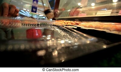 Close up Girls hand puts sushi container when buying. HD....