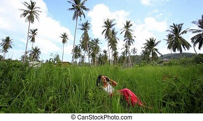 Young beautiful smiling woman lies on lawn and talks by mobile phone. Jungle in Koh Samui, Thailand. HD. 1920x1080