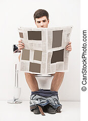 Young handsome man sitting on toilet and reading magazine....